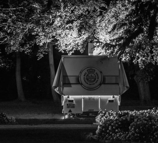 Moodshot Still Life mit Postproduction. Verkaufsstaende die von innen beuchtet sind in einer naechtlichen Umgebung. Die Atmosphaere oszilliert zwischen geheimnisvoll-spannend und pittoresk. Die Serie ist gänzlich in schwarzweiss gehalten. Neben den Staenden sind auch belaubte Baeume, Blumenrabatte, Sonnenschirme und Baenke zu sehen. Diese Bildreihe kann sowohl dem Genre Sachfotografie als auch Architekturfotografie zugerechnet werden.